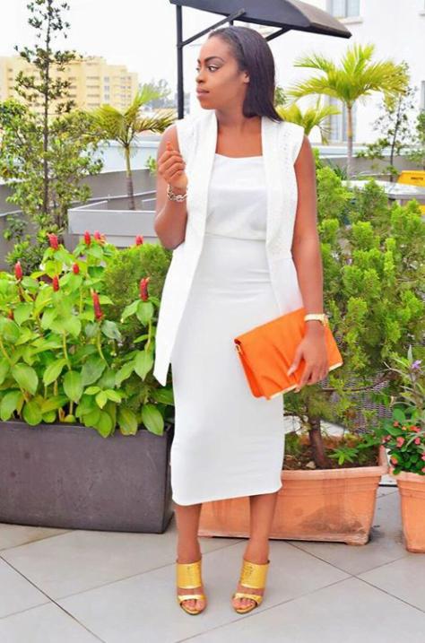 sleeveless blazer, blouse, midi skirt and burnt orange clutch
